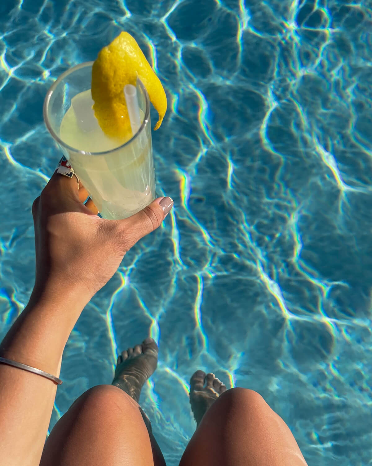 womans hands holding drink at pool